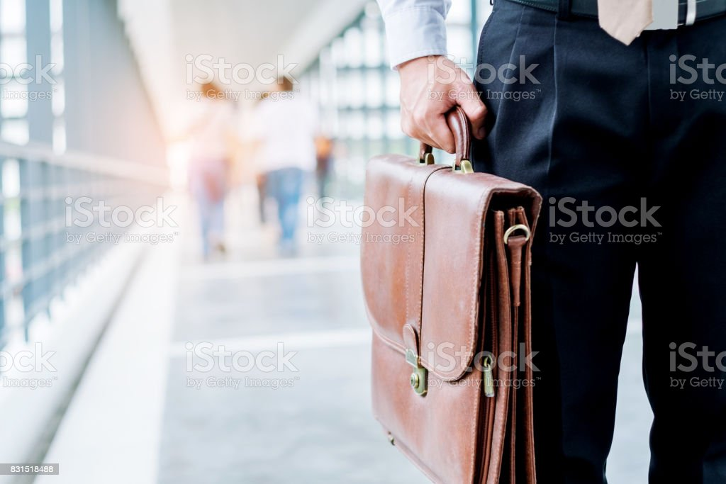 Businessman holding a briefcase travellers walking outdoors stock photo
