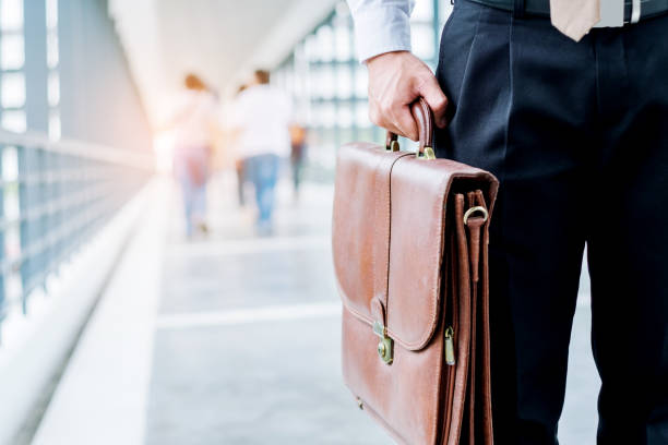 Businessman holding a briefcase travellers walking outdoors - foto stock