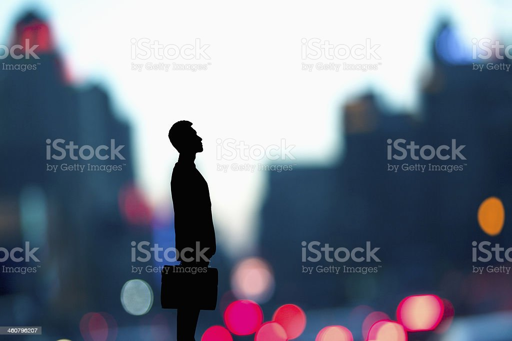 Businessman holding a briefcase with blurred city lights behind him stock photo