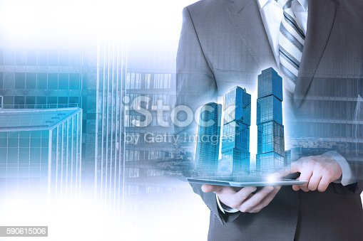businessman holding a building, skyscraper. The background of skyscrapers