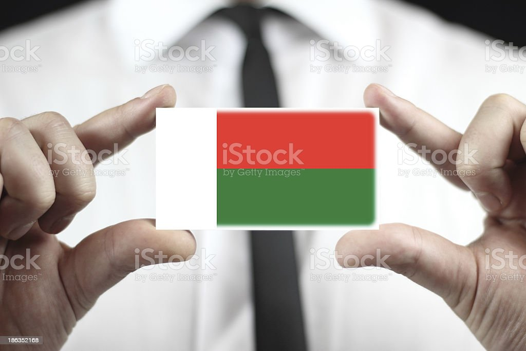 Businessman holding a business card with Madagascar Flag royalty-free stock photo