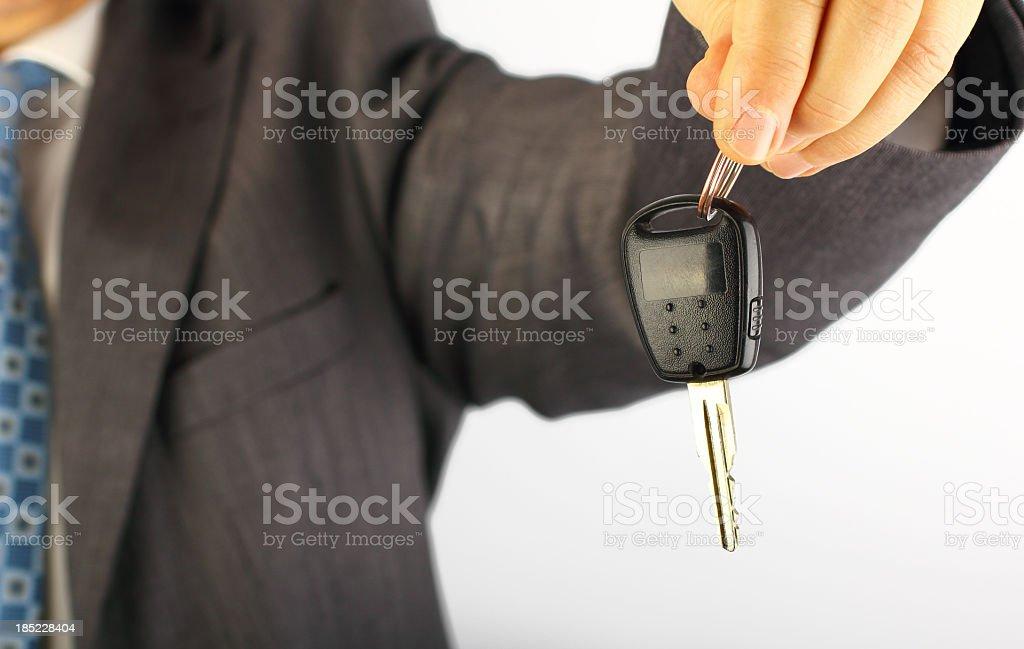 Businessman holding a car key royalty-free stock photo