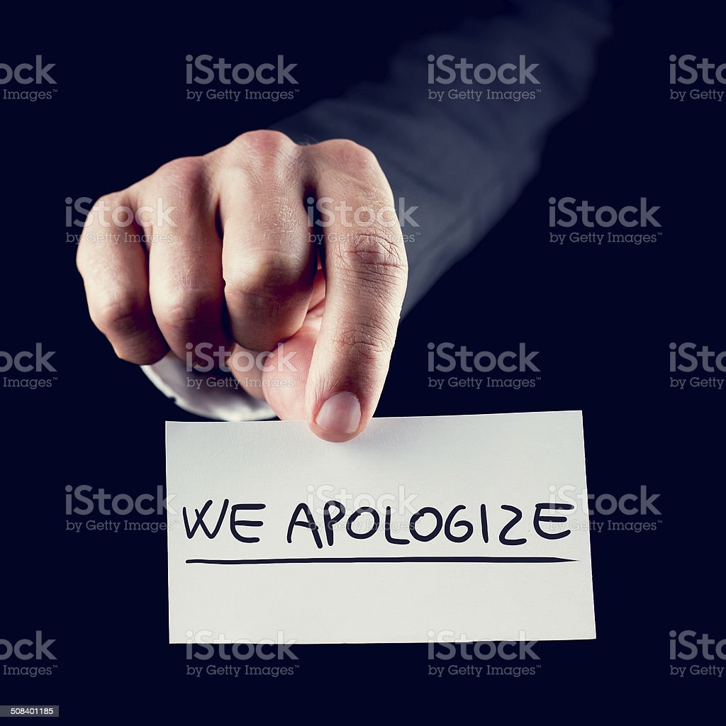 Businessman holding a card reading We Apologise stock photo
