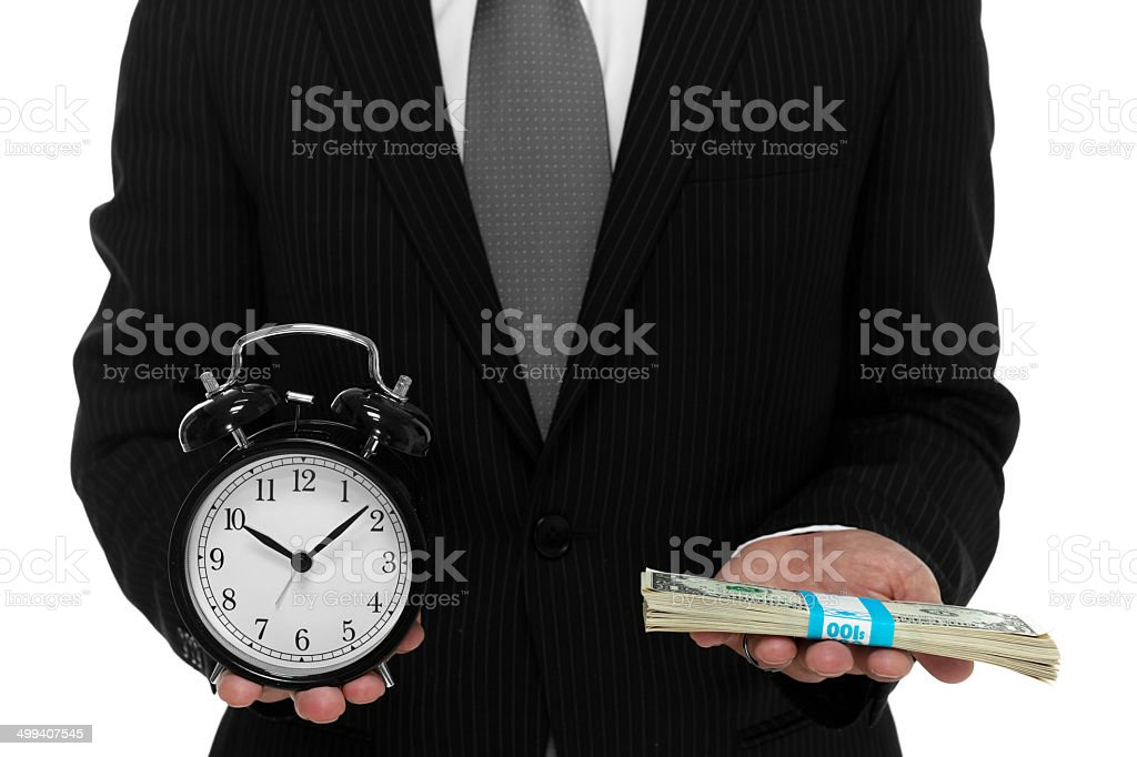 Businessman holding a clock and short stack of cash stock photo