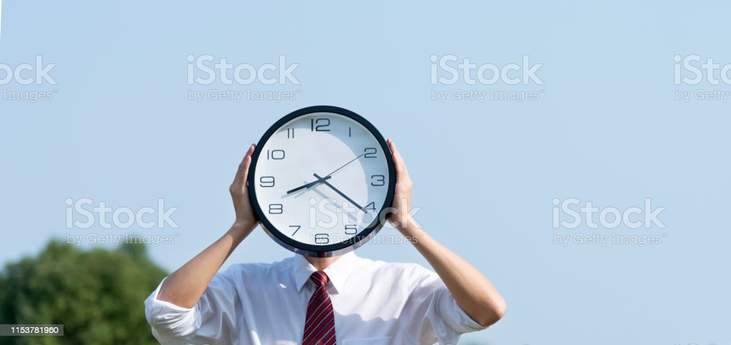 Businessman holding a clock in the open air.