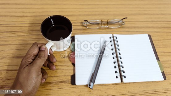1174436608 istock photo Businessman holding a cup of coffee. Business pocket planner with a eyeglass and a pen ready to note an appointment. Business still life concept with office stuff on table. Top view with copy space. 1134407199
