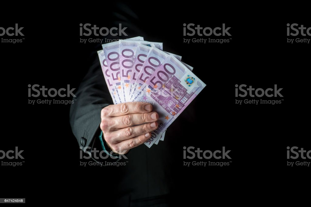 Businessman holding a fistful of 500 euro stock photo