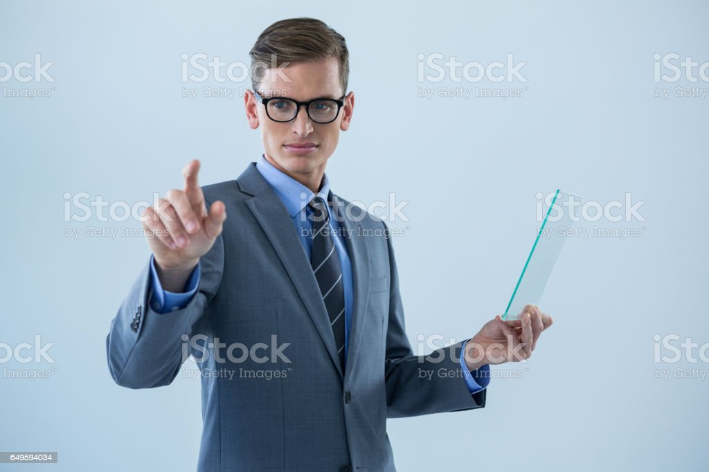 Businessman holding a glass sheet and touching an invisible screen stock photo