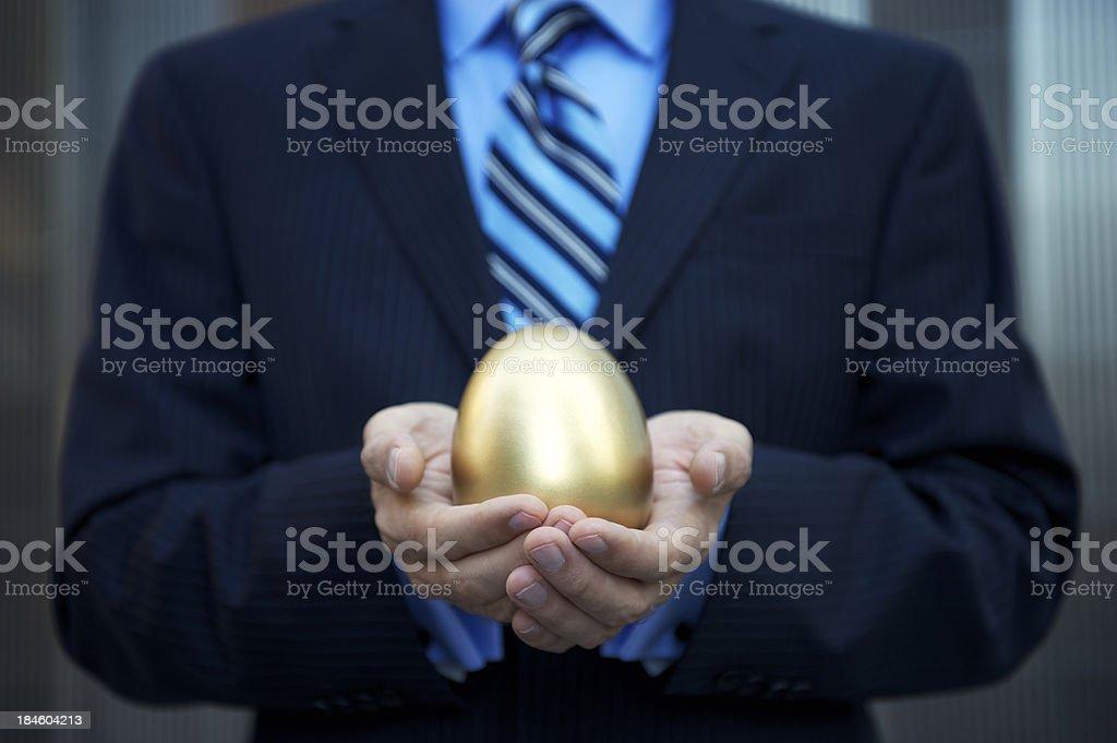 Businessman Holding a Golden Nest Egg Investment stock photo