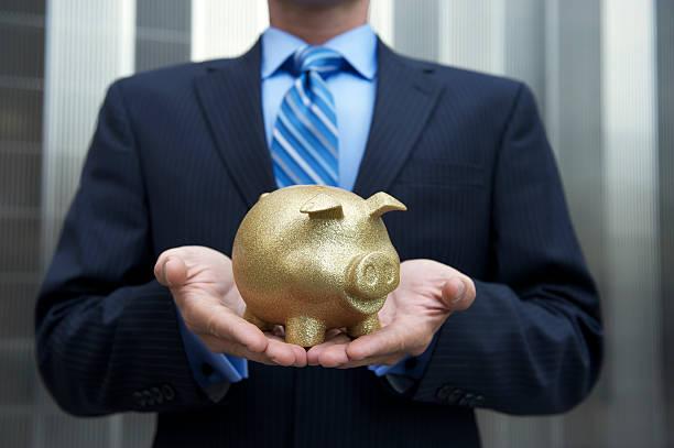 uomo d'affari tenendo un salvadanaio a porcellino d'oro all'aperto - bonus foto e immagini stock