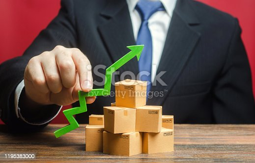 1155852718istockphoto Businessman holding a green arrow up over boxes. Boost sales rate. Increasing production of goods, expanding export opportunities, finding markets. Tactics and strategy, marketing. Value added goods 1195383000