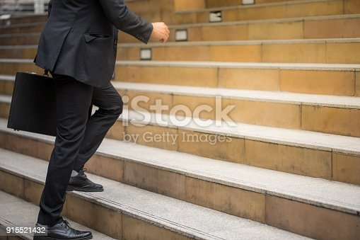 istock Businessman holding a handbag and running fast upstairs 915521432