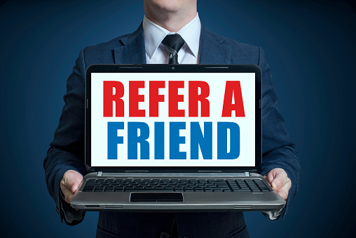 Businessman holding a laptop with text REFER A FRIEND