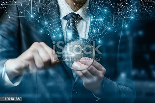 A closeup of a businessman holding magnifier and padlock behind it with wireless networking connections above at dark blurred background. The concept of comprehensive finance protection and security.