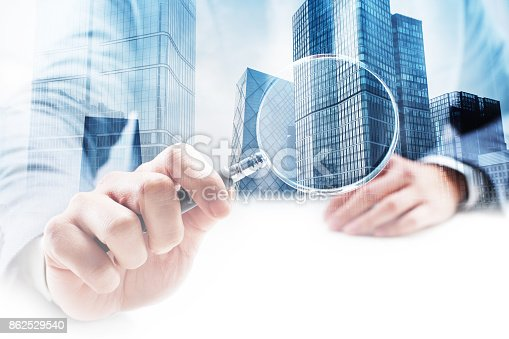 istock Businessman Holding a Magnifying Glass with Double Exposure Cityscape 862529540