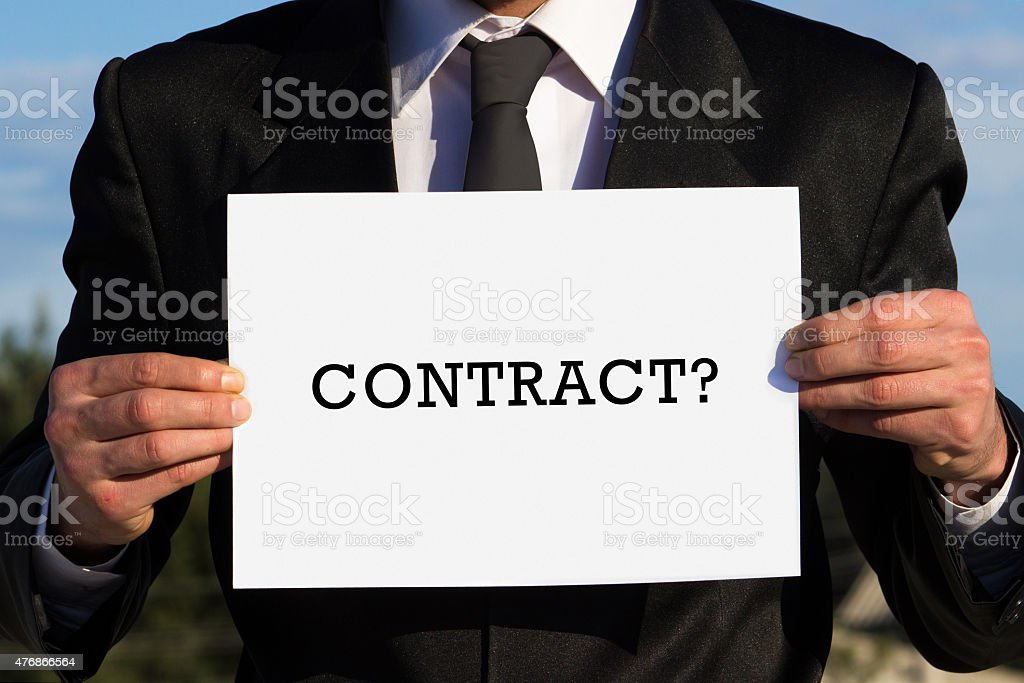 Businessman holding a paper writing on ''contract?'' stock photo