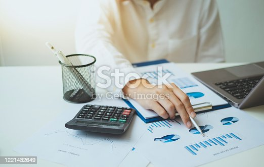 1068752548 istock photo Businessman holding a pen to point at the chart while he working with a laptop  and calculator to analyze business data on the desk. Financial and Business concept. 1221432649