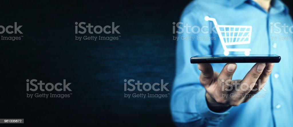Businessman holding a phone with a shopping icon. Online shopping stock photo