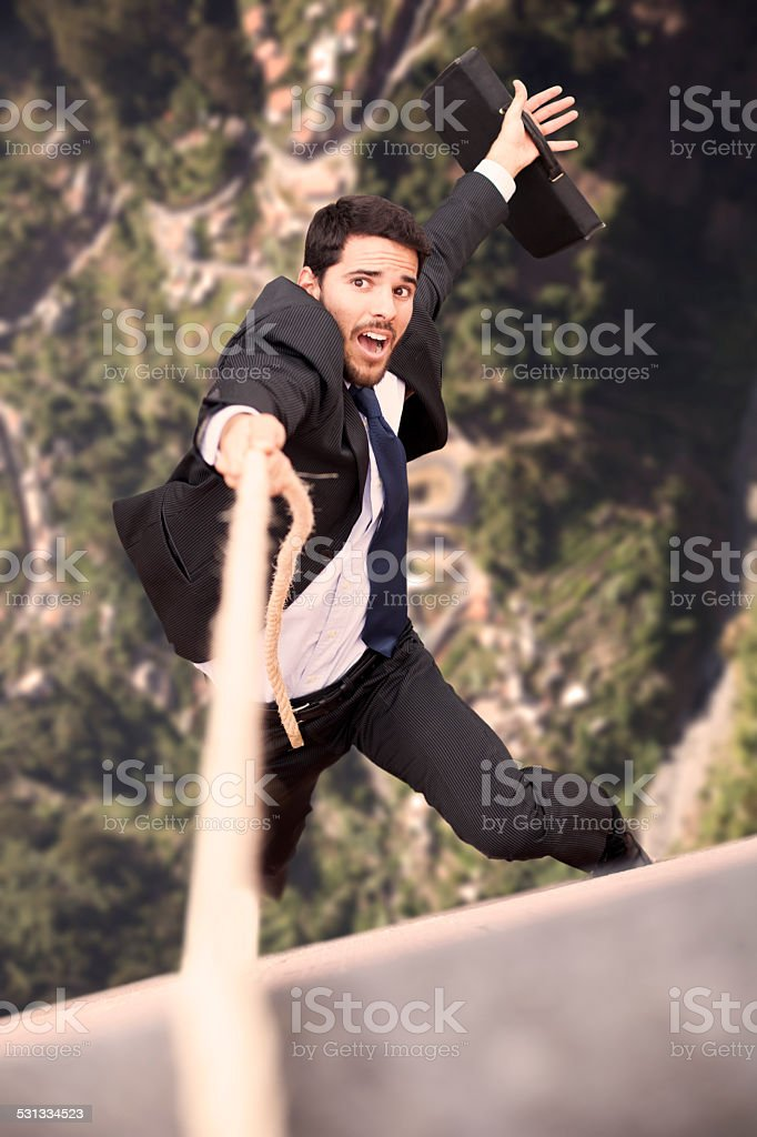 Businessman holding a rope at the cliff stock photo