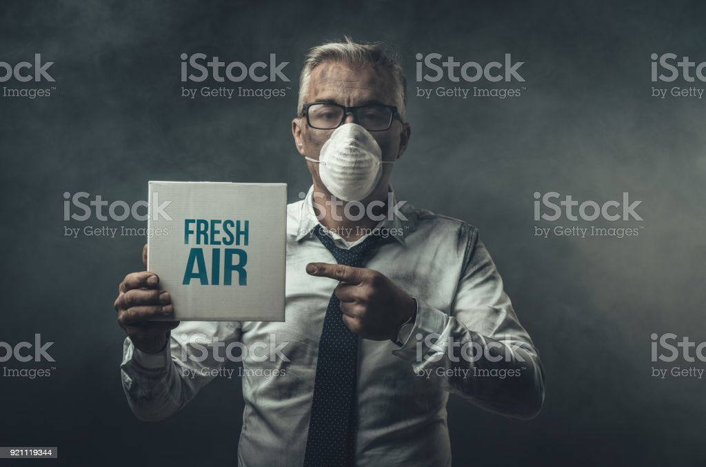 Businessman holding a sign and air pollution stock photo