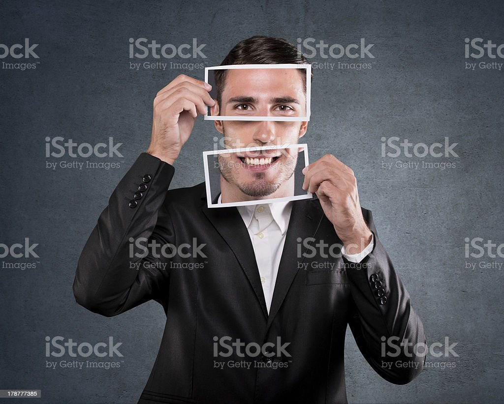 Businessman holding a smile over his face stock photo