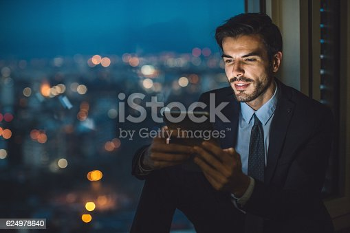 istock Businessman holding a tablet at night 624978640