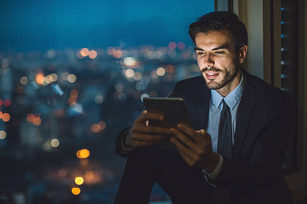 Businessman holding a tablet at night - foto de stock
