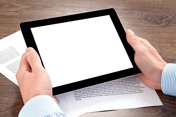 Homme d'affaires tenant une tablette avec des documents sur la table - Photo