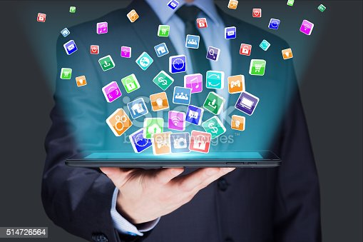 istock Businessman holding a tablet pc with mobile applications icons on 514726564