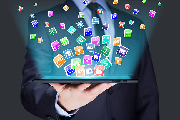 Businessman holding a tablet pc with mobile applications icons on stock photo