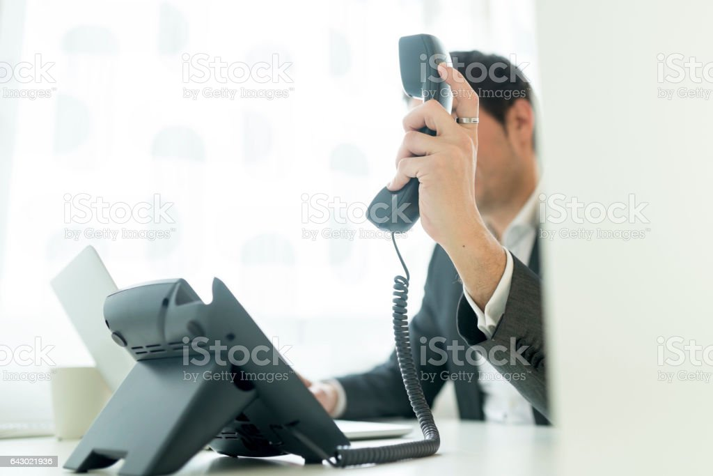 Businessman holding a telephone receiver stock photo