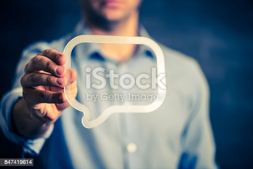 istock Businessman holding a transparent speech bubble 847419614