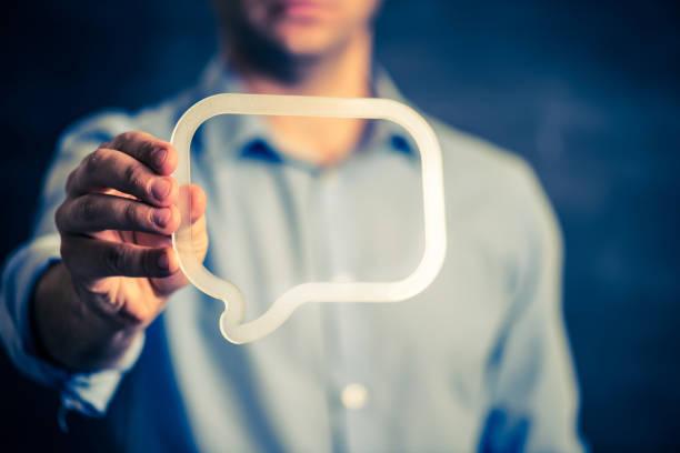 Businessman holding a transparent speech bubble stock photo