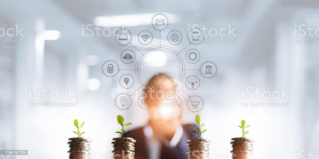 Businessman holding a tree sprout growing on coins, abstract growth...