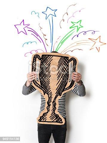 Businessman holding a trophy drawn on a piece of cardboard