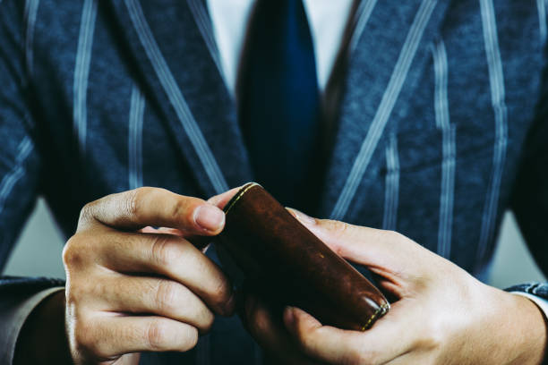 businessman holding a wallet - wallet stock pictures, royalty-free photos & images