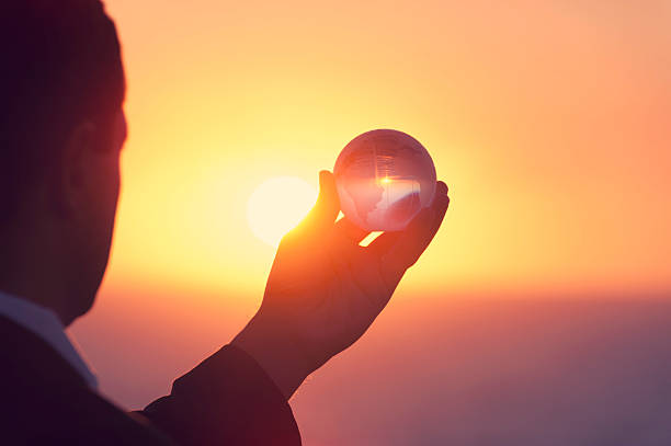 Businessman holding a world globe at dawn stock photo