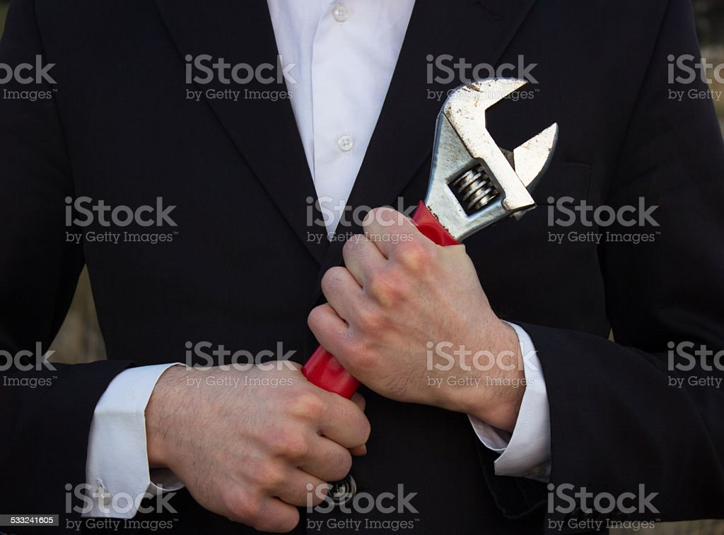 A photo of a businessman holding a wrench. Man wearing a suit.