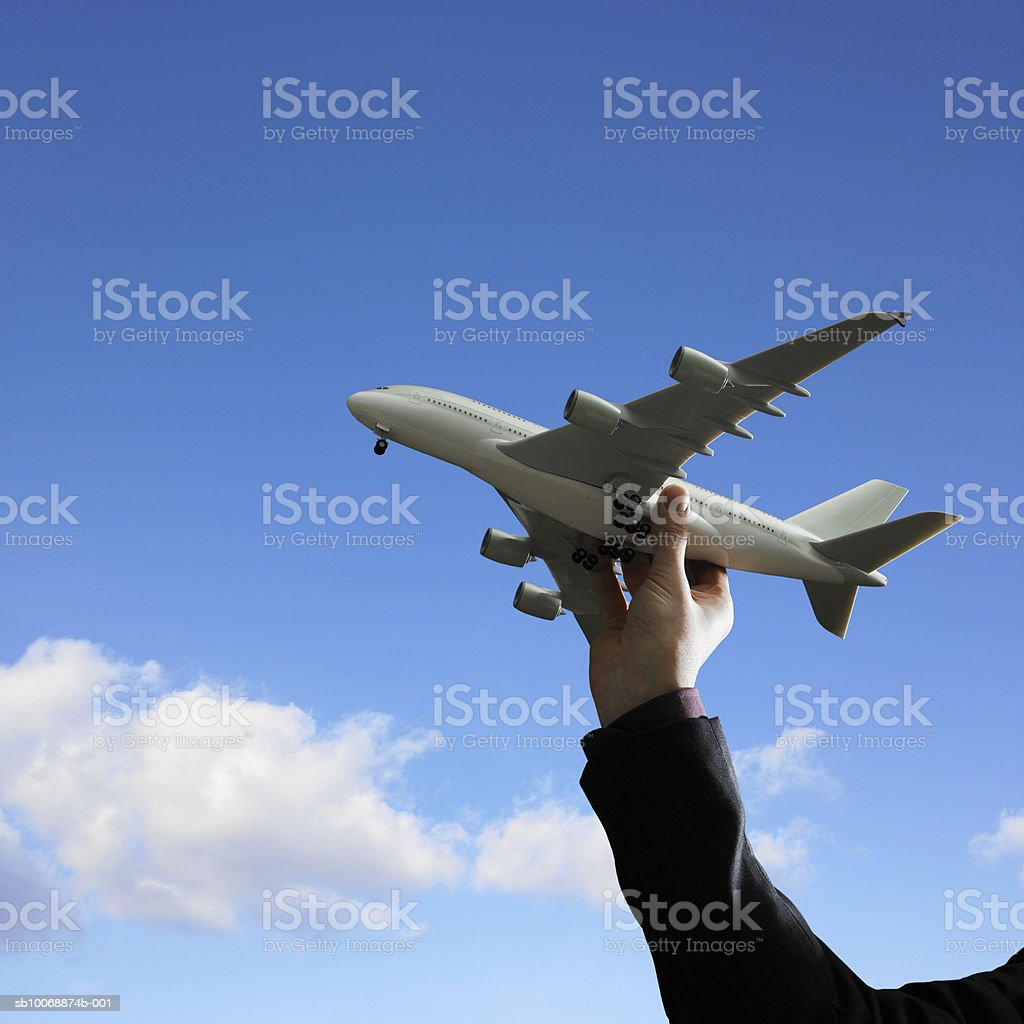 Businessman holding aeroplane against blue sky, close-up royalty-free stock photo