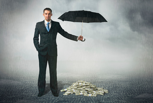 Businessman holding an umbrella over a pile of money