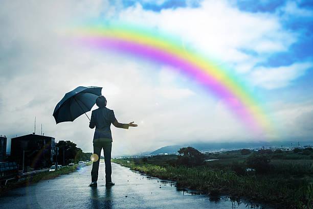 Businessman holding an umbrella, Rainbow and sky after the rain stock photo