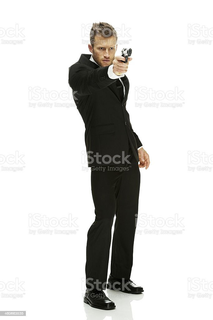 Businessman holding and pointing a gun stock photo