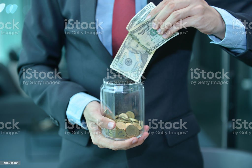 Businessman holding and saving money banknotes in a wooden jar stock photo