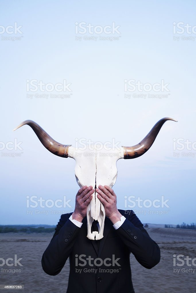 Businessman holding animal skull in front of face stock photo