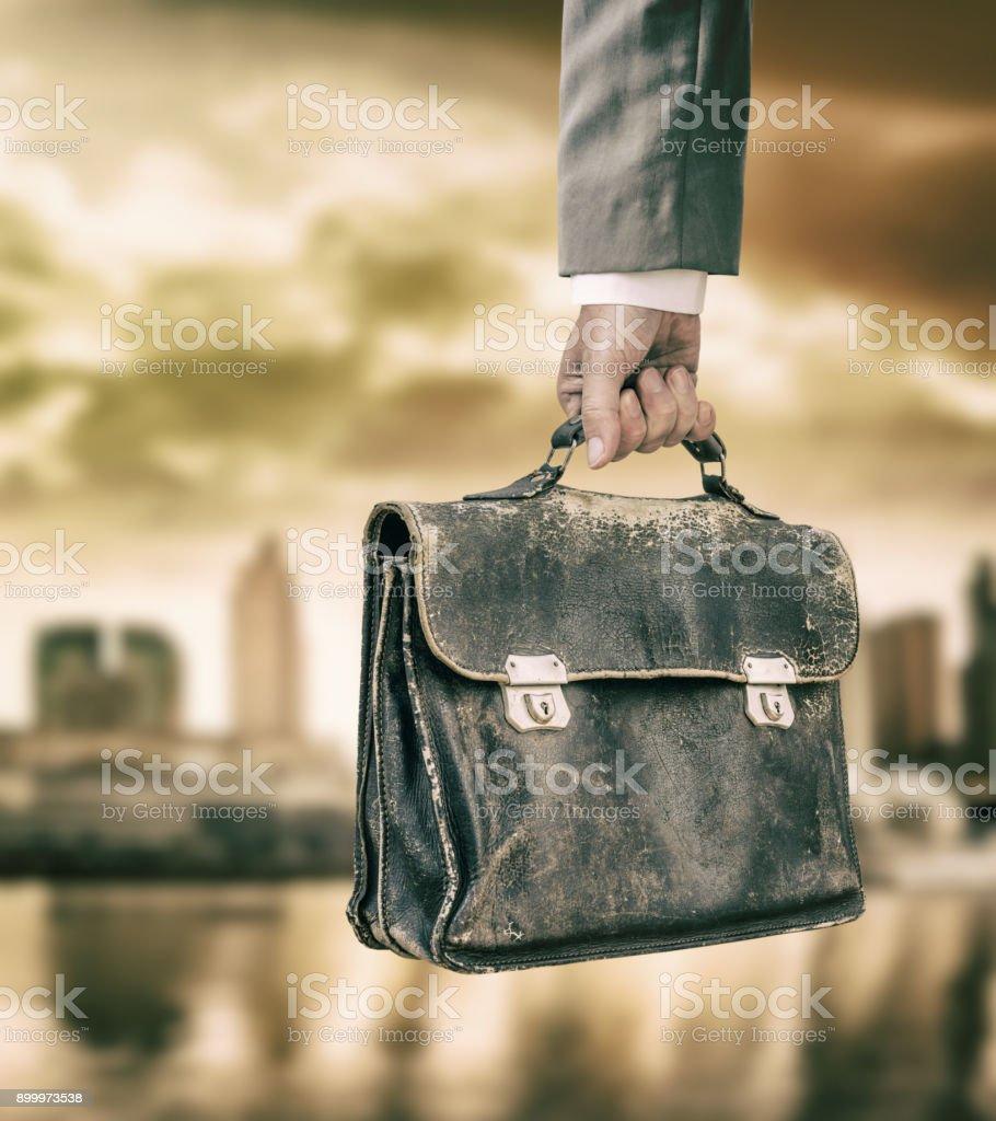 Empresário, segurando a mala de couro antigo na frente da cidade - foto de acervo