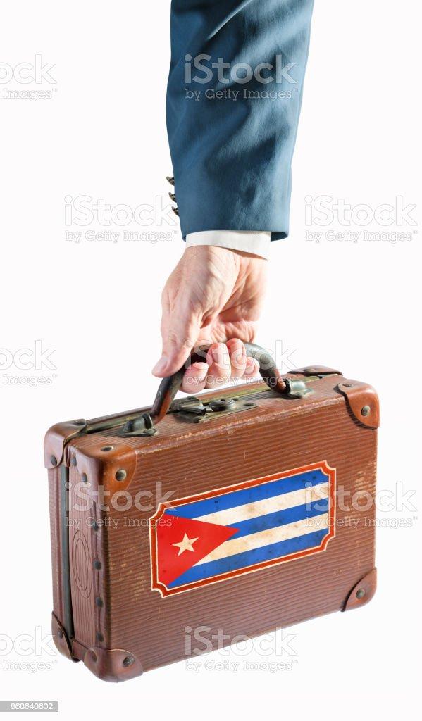 Empresário, segurando a mala antiga com bandeira de Cuba - foto de acervo