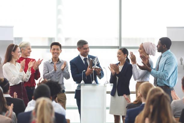 businessman holding award op het podium met collega's in een business seminar - prijs onderscheiding stockfoto's en -beelden
