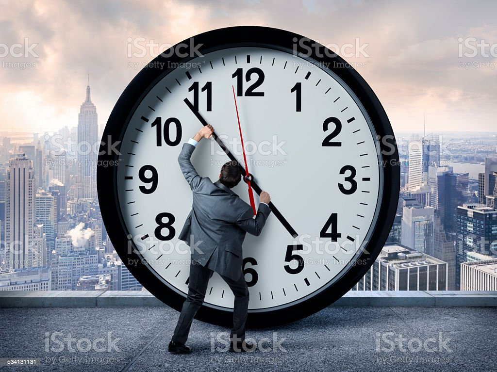 Technology Management Image: Businessman Holding Back The Hands Of Time Stock Photo