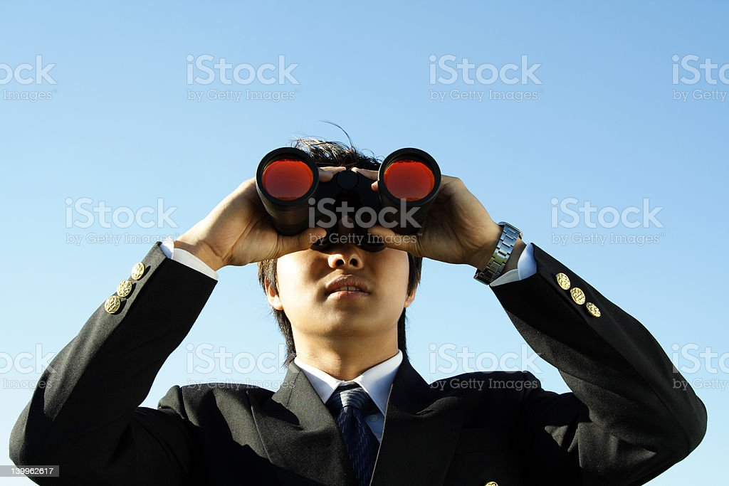 Businessman holding binoculars at his eyes royalty-free stock photo