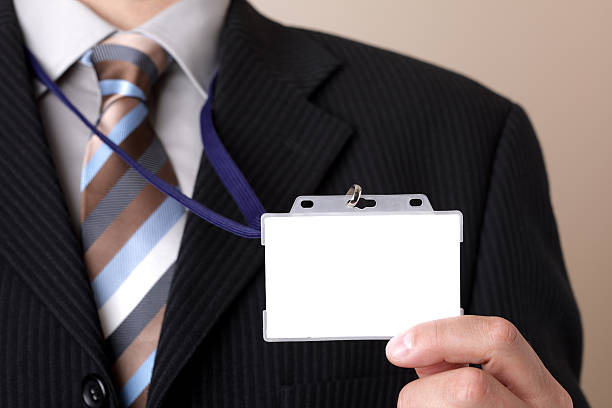 Businessman holding blank ID badge Businessman showing a blank identity name card security pass stock pictures, royalty-free photos & images